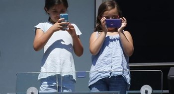Young girls take pictures with the cell phones during the match between Victoria Azarenka of Belarus and Christina McHale of the U.S. at the 2014 U.S. Open tennis tournament in New York, August 28, 2014.