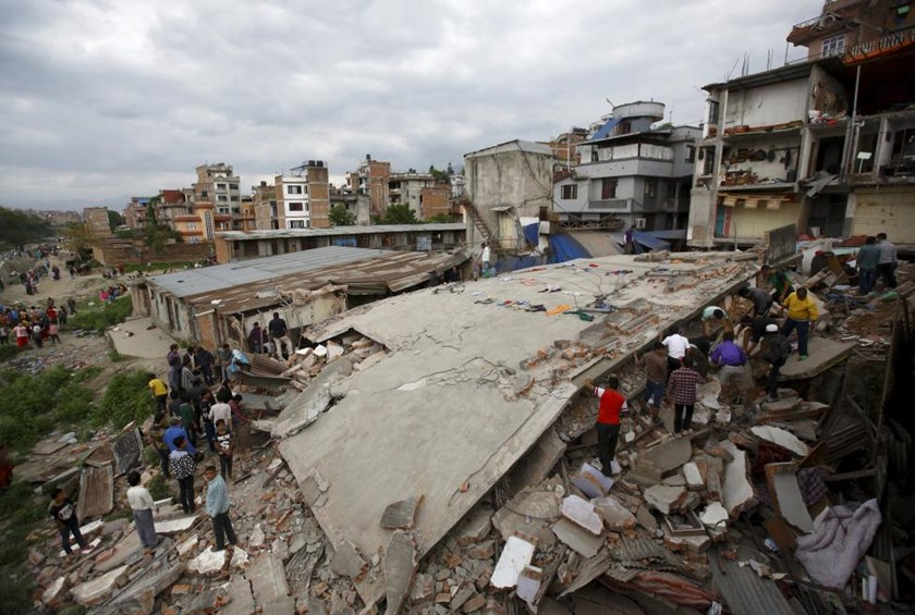 People gather near a collapsed house after a major earthquake in Kathmandu, April 25, 2015.