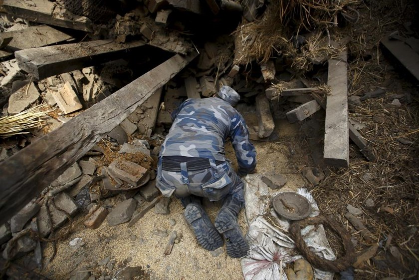 Rescue team member works to dig out the trapped body of a woman from a collapsed house in Bhaktapur, April 26, 2015.