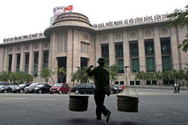 A man walks past the State Bank of Vietnam in Hanoi.