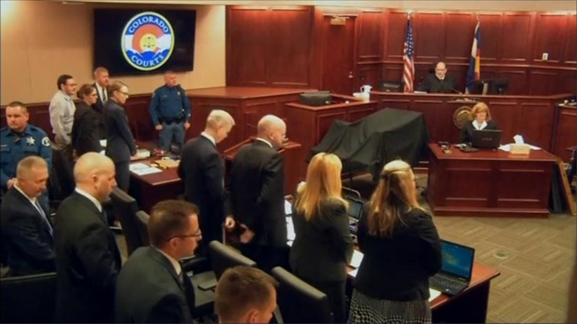 James Holmes (2nd L) stands at the start of his trial in Arapahoe County District Court in Centennial, Colorado in this still image captured from a pool video footage April 27, 2015. REUTERS