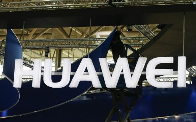 A worker adjusts the logo at the stand of Huawei at the CeBIT trade fair in Hanover March 15, 2015.