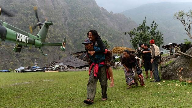 A Nepalese resident injured in the recent earthquake is carried by a relative towards an Indian Army helicopter as others follow at Lapu, in Gorkha, on April 28, 2015.