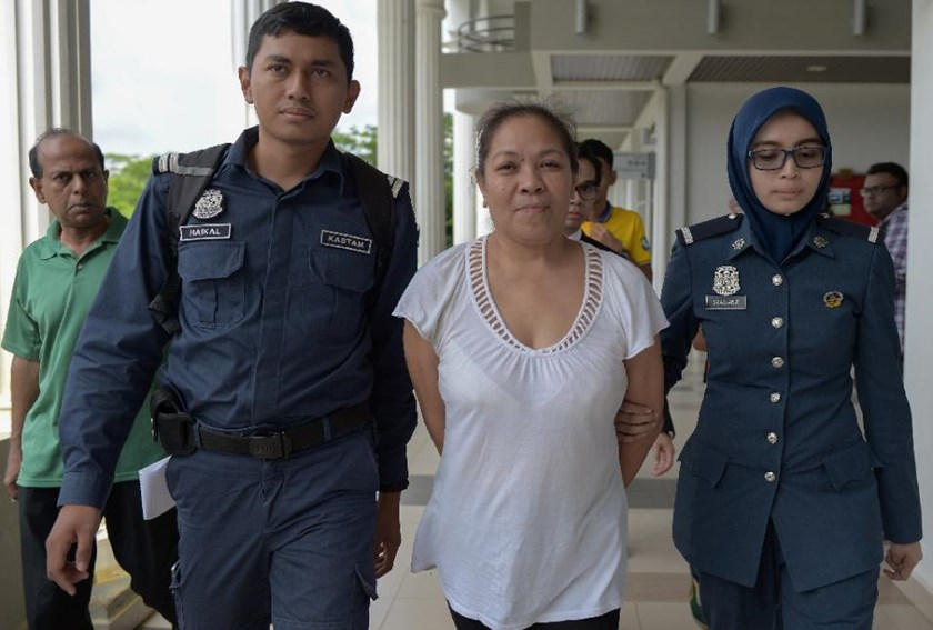 Australian national Maria Elvira Pinto Exposto (2nd R) is escorted by Malaysian customs officials as she arrives at the Magistrate Court in Sepang on April 30, 2015
