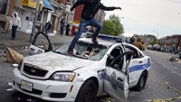 Demonstrators jump on a damaged Baltimore police department vehicle during clashes after the funeral of Freddie Gray, who died in police custody in Baltimore, Maryland, April 27, 2015.