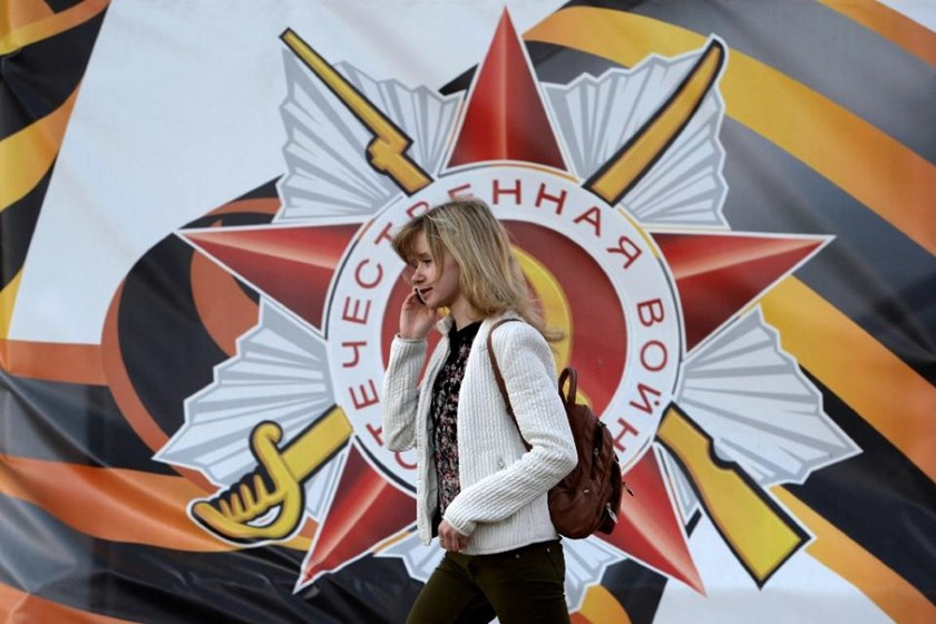A woman passes a banner for the upcoming Victory Day celebrations in Moscow on April 28, 2015