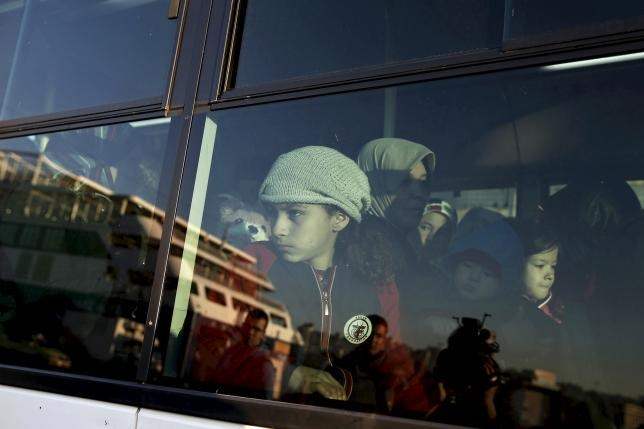 A young undocumented migrant that entered Greece through its sea borders is seen through a bus