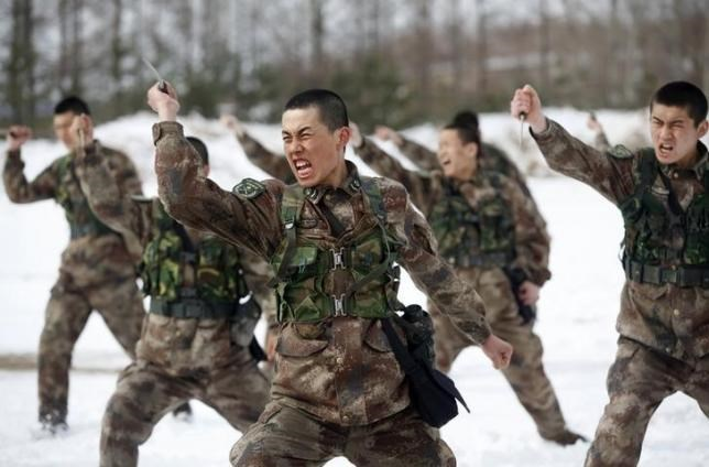 People's Liberation Army (PLA) soldiers shout as they practise with knives during a training session on snow-covered ground at a military base in Heihe, Heilongjiang province March 18, 2015.