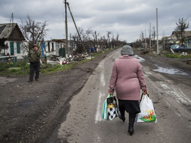 A woman carries walks back to the village of Nikishino in Ukraine, on April 21, 2015. Photo: AFP