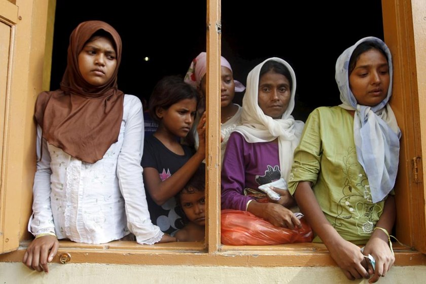 Migrants, believed to be Rohingya, look out the window of a shelter they are staying at since being rescued along with hundreds of others on Sunday from boats in Lhoksukon, Indonesia's Aceh Province May 12, 2015.