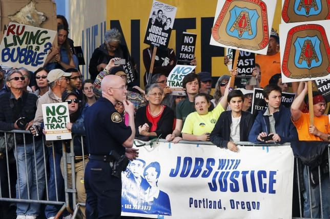 Protesters, many against the so-called fast track trade authority of the Trans-Pacific Partnership (TPP) trade agreement, rally outside the hotel where U.S. President Barack Obama is participating in a Democratic National Committee (DNC) event in Portland