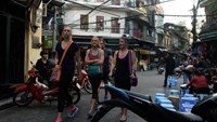 Foreign tourists walk in Hanoi downtown. Photo credit: AFP