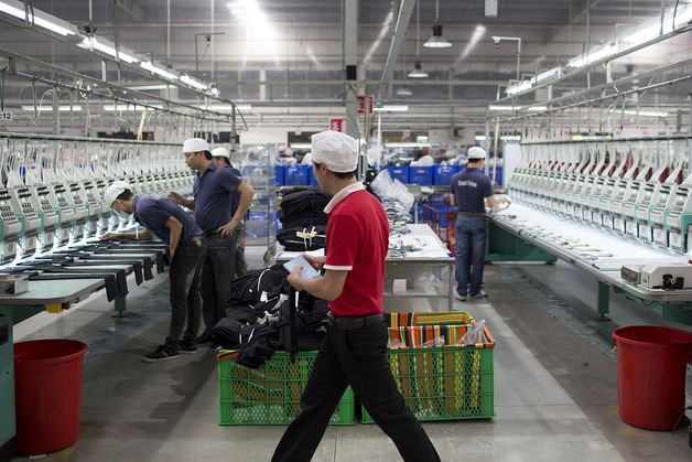 Workers arrange pieces of fabric under embroidery machines inside the Esquel Group garment factory at the Vietnam-Singapore Industrial Park in Thuan An, Binh Duong province, Vietnam. Photo: Bloomberg