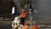 A protester, who is against President Pierre Nkurunziza's decision to run for a third term, gestures in front of a burning barricade in Bujumbura, Burundi May 14, 2015.