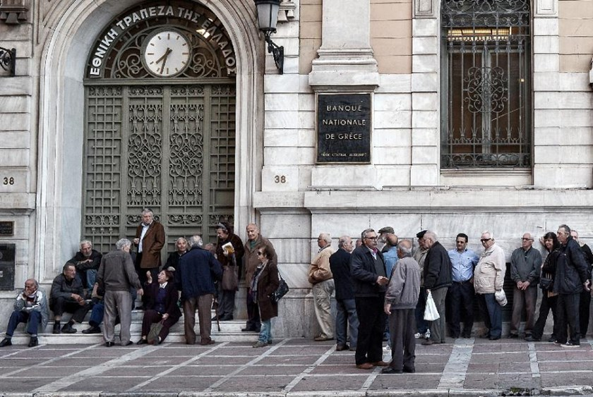 Pensioners wait outside the National Bank of Greece in Athens to get their monthly pensions on April 29, 2015