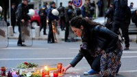People light candles in front of the riot policemen to commemorate policemen who were killed after fighting between Macedonian police and an armed group in the town of Kumanovo in Skopje on May 11, 2015