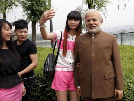 A woman poses for a selfie with a silica gel sculpture of Indian Prime Minister Narendra Modi, which was made by local sculpture artists, at a park in Xian.