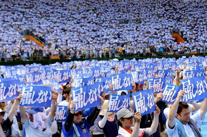 "An estimated 35,000 protesters raise placards saying ""Do not yield to authority"" during a rally to protest against a controversial US airbase in Naha in Japan's southern island of Okinawa on May 17, 2015"