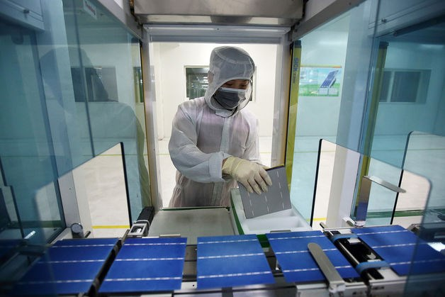 An employee inspects solar cells moving along the production line at the Trina Solar Ltd. factory in Changzhou, Jiangsu Province, China.