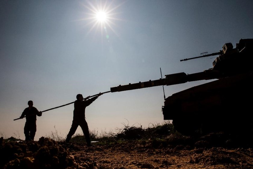 Israeli soldiers work on their tank along the border with Lebanon on January 20, 2015. Photo: AFP