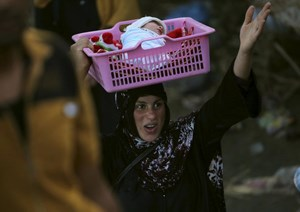 An Iraqi Sunni displaced woman, who fled the violence in the city of Ramadi carries her child on the outskirts of Baghdad, Iraq May 19, 2015.