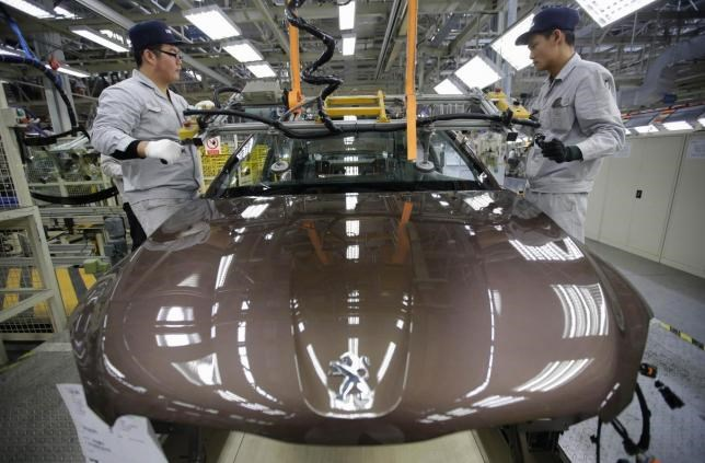 Employees work at a production line of a Dongfeng Peugeot Citroen Automobile factory in Wuhan, Hubei province, February 13, 2014.