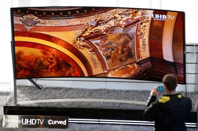 A visitor takes photographs of a Samsung Electronics' 105-inch Curved Ultra High Definition (UHD) TV at the company's headquarters in Seoul January 28, 2015.