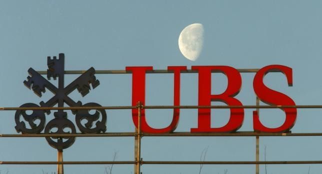 A file picture shows the waning moon behind a logo of Swiss bank UBS in Zurich, Switzerland February 10, 2015.