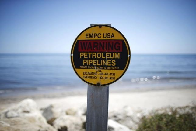 A sign warns of petroleum pipelines next to an oil slick along the coast of Refugio State Beach in Goleta, California, United States, May 20, 2015.