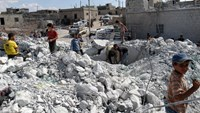 Syrians check a damaged house, reportedly hit by US-led coalition air strikes, in the village of Kfar Derian in the western Aleppo province on September 23, 2014. Photo: AFP