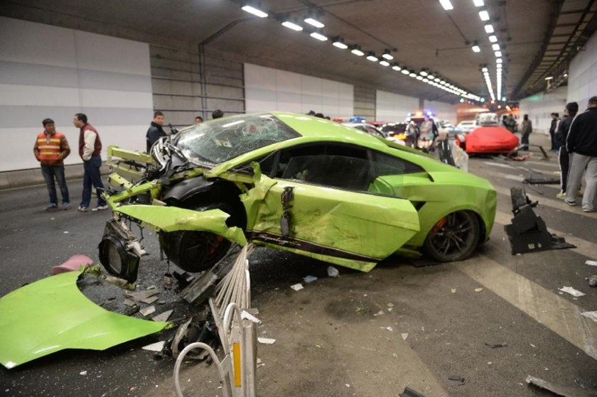 Chinese officials inspect the mangled wreckage of a Lamborghini that was damaged in a high-speed illegal road race in Beijing, on April 12, 2015