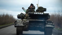 Pro-Russian separatist soldiers stand on their tank as they drive along a road near the village of Kirovske on April 21, 2015 in the self-proclaimed Donetsk People's Republic