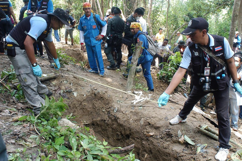 Thai police officials measure a shallow grave in Padang Besar, Songkhla province, southern Thailand.