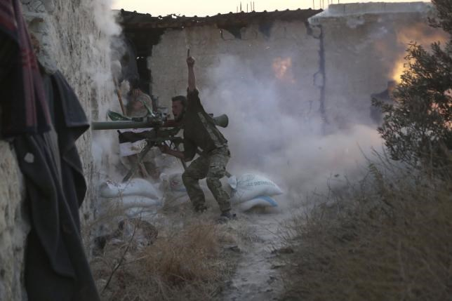 A rebel fighter gestures as he shoots his weapon during clashes with forces loyal to Syria's President Bashar al-Assad on the frontline of Aleppo's Sheikh Saeed neighbourhood May 23, 2015.