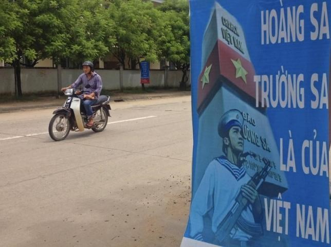 A man rides a motorcycle past a poster promoting Vietnam' sovereignty in the East Sea (South China Sea) on Phu Quoc island September 11, 2014.