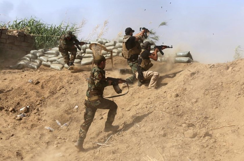 Iraqi Sunni fighters battling Islamic State (IS) group jihadists alongside government forces fire their weapons on the outskirts of Iraq's Baiji oil refinery on May 25, 2015