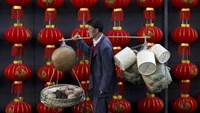 A basket vendor walks past red lanterns serving as decorations to celebrate the new year outside a shopping mall in Kunming, Yunnan province January 6, 2015.