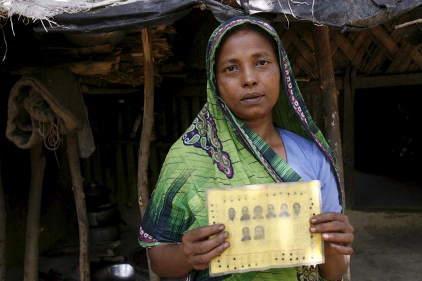 Rupban, a Rohingya woman, shows her ration card with pictures of her family members at a refugee camp in Kutupalong May 31, 2015.