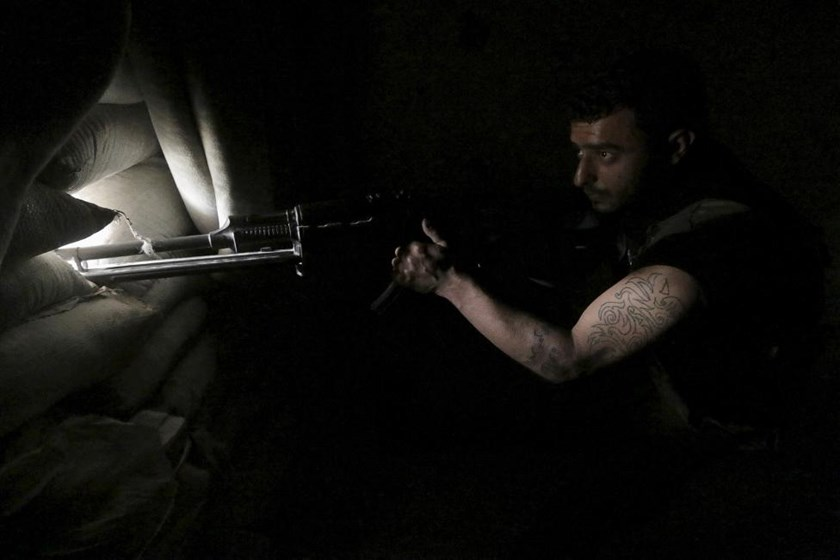 A rebel fighter takes position behind sandbags in Aleppo's Al-Ezaa neighborhood, Syria, May 20, 2015.