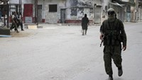 Members of al Qaeda's Nusra Front walk along a street in the northwestern city of Ariha