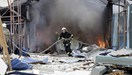 A firefighter works to extinguish a fire at a local market, which was recently damaged by shelling, in Donetsk, Ukraine, June 3, 2015.