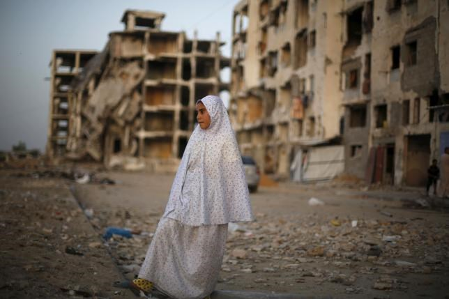 A Palestinian girl stands near residential buildings that witnesses said were heavily damaged by Israeli shelling during a 50-day war last summer.