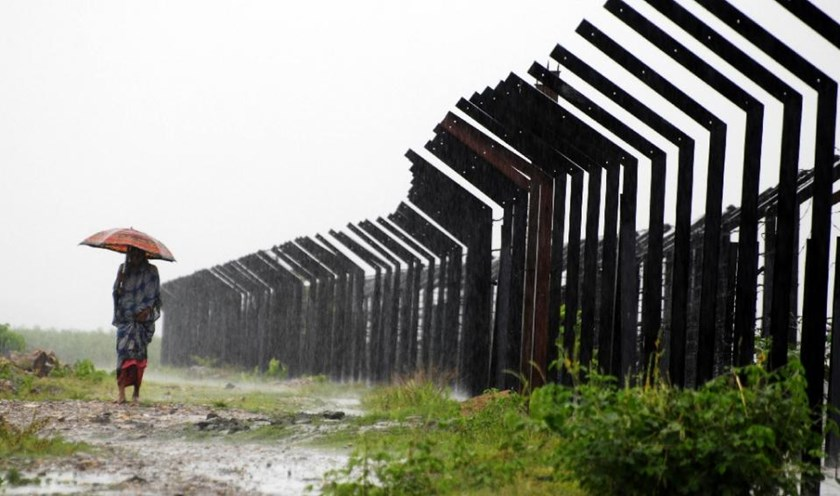 An Indian woman walks in the rain along the Indo-Bangladesh border at the Masalabari border outpost in the Dhubri district of Assam state, on July 30, 2009