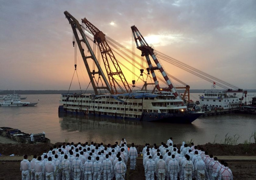 Rescue workers stand on the river bank as the capsized cruise ship Eastern Star is pulled out of the Yangtze against sunset, in Jianli, Hubei province, China, June 5, 2015.