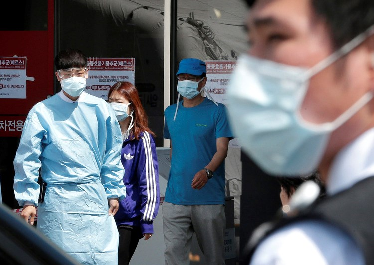 Hospital workers and visitors pass signs about MERS at Seoul National University Hospital on June 3, 2015. Photographer: Ahn Young-joon/AP Photo