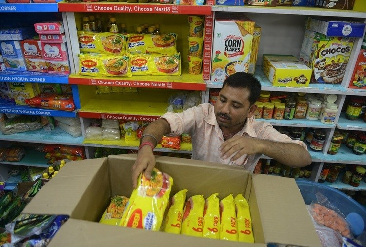 An Indian shopkeeper removes packets of Nestle 'Maggi' instant noodles from the shelves in his shop in Siliguri, India. Photo: AFP