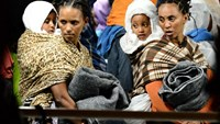 "Migrants and their children wait to disembark from the ""Phoenix"" ship upon their arrival in the port of Augusta on the eastern coast of Sicily on June 7, 2015"