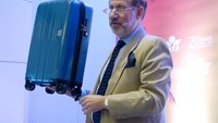 International Air Transport Association (IATA) senior vice president for airport, passenger, cargo and security, Tom Windmuller, holds up the group's proposed ideal-sized carry on bag