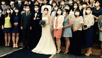 A South Korean couple and their wedding guests pose for a photo wearing masks in Seoul on June 6, 2015