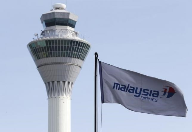 A Malaysian Airlines flag flies in front of the traffic control tower at Kuala Lumpur International Airport in Sepang July 18, 2014.